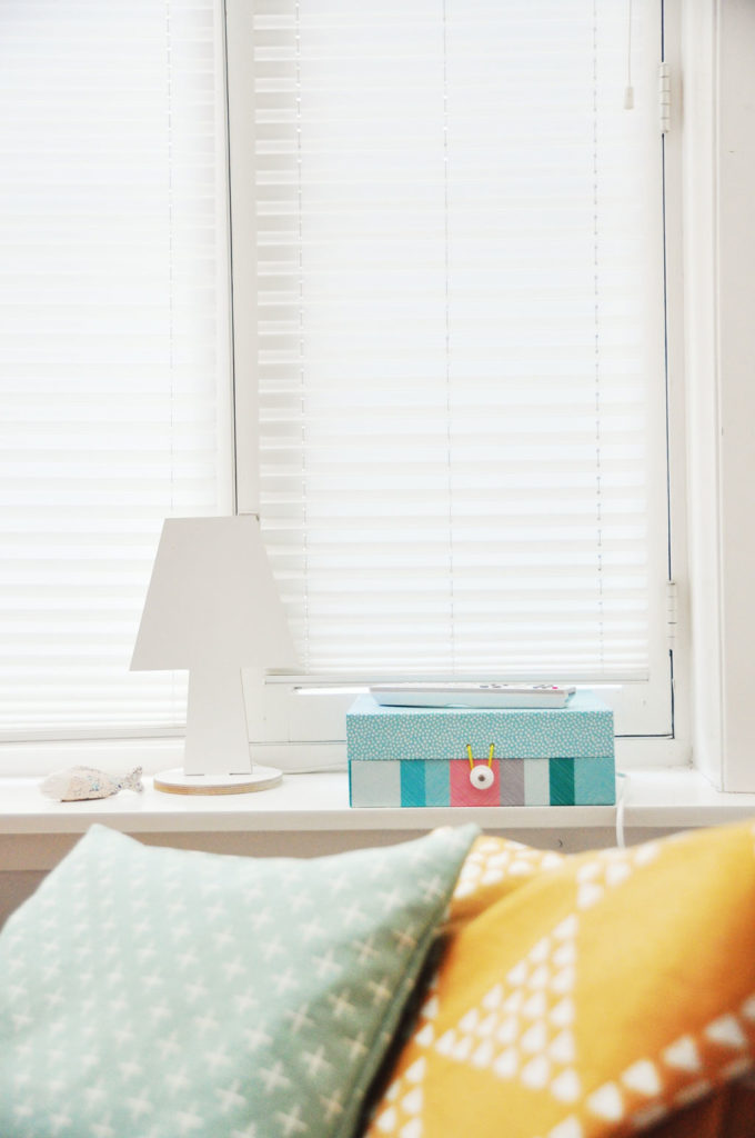 blind covered window with light shinging through onto windowsill and two cushions