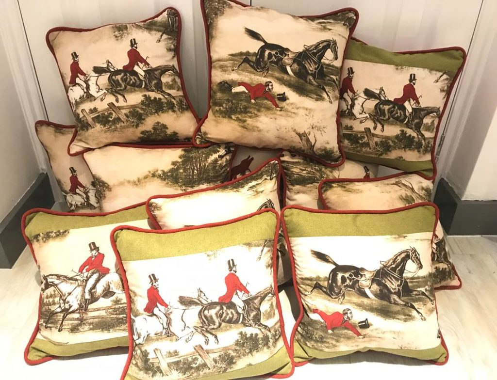 collection of cushions patterned with illustrations of men in top hats and red coats riding horses through fields